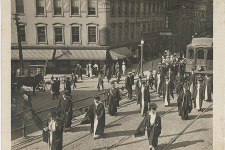 Aged photograph of a parade of women in academic caps and gowns marching along a raised roadway in front of a streetcar. A busy street and a billiard academy are visible in the background.