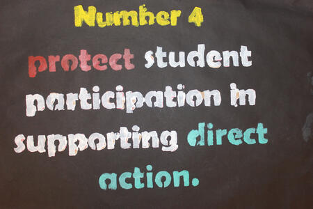 Poster with strike demand number 4, created with a stencil made by Daniela Moreira
